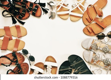 Set of various leather sandals and sunglasses on white background. Casual summer accessories, top view point.