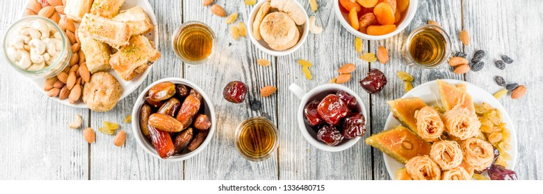 Set various Middle Eastern Arabian sweets - Turkish baklava, knafeh (kunaf), nuts, dried fruits and seeds. White wooden background, top view copy space banner