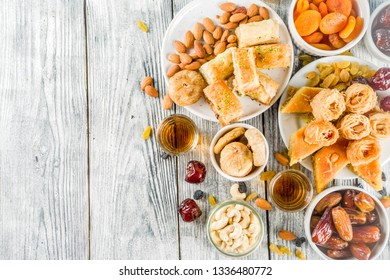 Set various Middle Eastern Arabian sweets - Turkish baklava, knafeh (kunaf), nuts, dried fruits and seeds. White wooden background, top view copy space