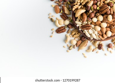 set of various nuts in wooden plates on white background with copy space