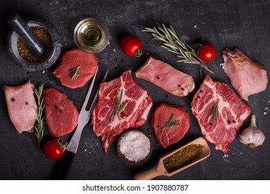 Set of various  raw meat on wooden cutting board at kitchen table