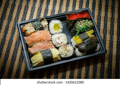Set of various rolls in black plastic box. Rolles collection with crab sticks, salmon, sockeye salmon, coho salmon, masago caviar, wakame, shiitake mushrooms, eel, radish, nori seaweed.