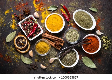 Set of Various spices and condiments on dark stone table. Chilly pepper, rosemary, basil, turmeric, paprika, garlic, anise, cinnamon and other. Top view.