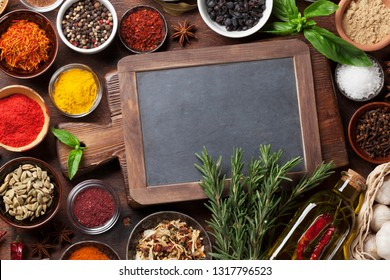 Set of various spices and herbs on wooden background. Top view with chalkboard for your recipe. Flat lay