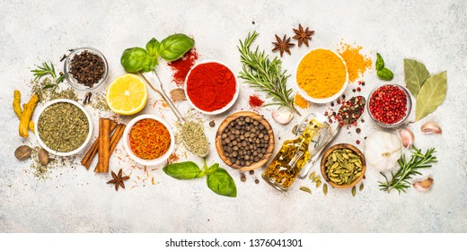 Set of various spices and herbs on light stone table. Pepper, turmelic, saffron, basil, rosemary, chilly, cardamom, cinnamon, anise. Top view. Long banner format.