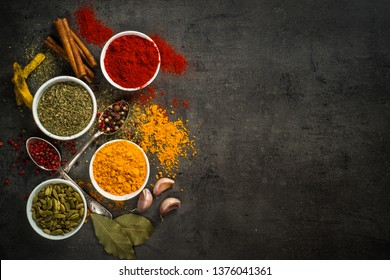 Set of various spices on black background. Pepper, turmelic, paprika, basil, rosemary, chilly, cardamom, cinnamon, anise. Top view with copy space.