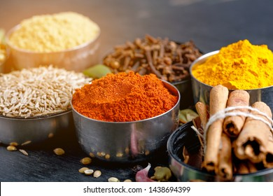Set of various spices on black background. Pepper, turmeric, paprika, chilly, cumin, cloves, coriander, cardamom, cinnamon, anise. Top view with copy space.