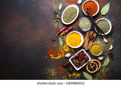 Set of Various spices on dark stone table. Chilly pepper, rosemary, basil, turmeric, paprika, garlic, anise, cinnamon and other. Top view with copy space.