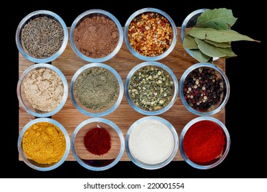 Set of various spices on wooden plank  isolated on black