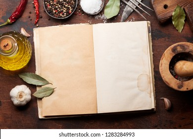 Set of various spices in spoons on wooden background. Top view with cookbook for your recipe. Flat lay