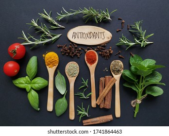 Set of various spices in wooden spoons and fresh herbs rich in antioxidants. Natural sources of antioxidants rosemary twigs, fresh green basil leaf, mint leaf, turmeric, clove, cinnamon, chili, tomato
