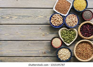 A set of various superfoods - whole grains,beans, seeds, legumes in bowls on a wooden plank table. Top view, copy space