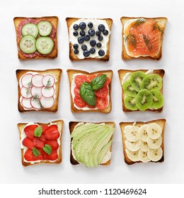 Set of various toasts with fruit, vegetable, fish and sausage and cheese on white baking paper top view.