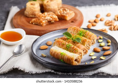 Set of various traditional arabic sweets: baklava, kunafa, basbus in  ceramic plates on a gray concrete background. side view, selective focus.