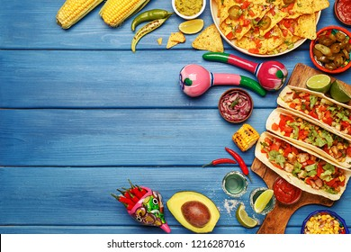 Set of various traditional mexican food on blue wooden background. Tacos, nachos, corn cobs, grilled corn, tequila shots, vegetables and sauces, maracas. Top view, copy space