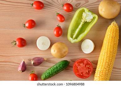 A set of vegetables laid out on a wooden table. Flat lay,top view. Free space for text.