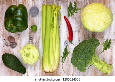 Set of vegetables on white painted wooden background: kohlrabi, pepper, cabbage, broccoli, avocado, rucola, brussels sprouts, celery.
