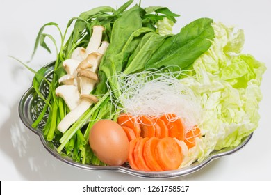 Set of vegetables in Stainless steel tray for healthy food and good for life, organic egg, sliced mushrooms, preparing fresh vegetables set for sukiyaki and served with soup, suki sauce, clean food