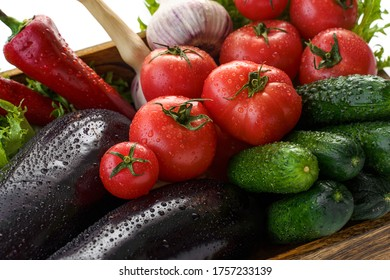 Set of vegetables in wooden box(tomatoes, eggplants, cucumbers, sweet peppers, salat and garlic) isolated on white background. Closeup. - Shutterstock ID 1757233139
