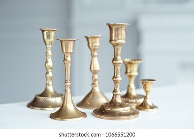 Set of Vintage Brass Candlesticks on white table indoor.