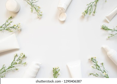 Skin​care​ packaging​​ set w/ spring flowers on​ white​ background.​ Natural beauty​ cosmetology​ concept.​ Copy​ space​ for​ text or​ mock-up​ cosmetic​ branding​ products.​ Top​ view. Flat lay.