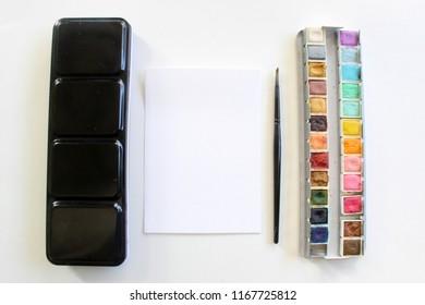 set of watercolor paints, brush and paper. watercolor mockup scene.