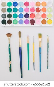 Set of Watercolor Paints and Brushes with Colorful, Bright Paint Splatters