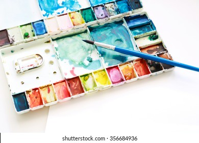 Set of watercolor paints, brushes for painting and blank white water color paper sheet of sketchbook on white background. Creation process of watercolor painting. Top view.