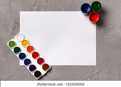 A set of watercolor paints, cans with gouache and blank sheet of white sketchbook paper on a concrete background. Copyspace