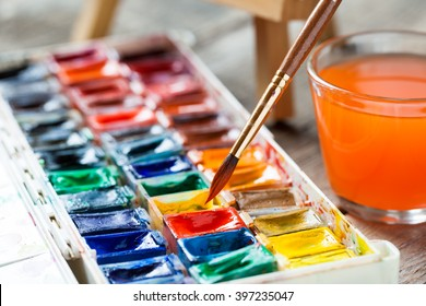 Set of watercolor paints and paintbrushes for painting closeup. Selective focus.