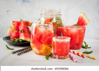 Set of watermelon summer drinks and cocktails: sangria, juice cooler cocktail, infused detox water, watermelon vodka shot. On a white marble table. Copy space