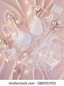 Set of wedding white lace underwear lingerie on background of pink delicate silk with silver festive glass balls with shining lights top view