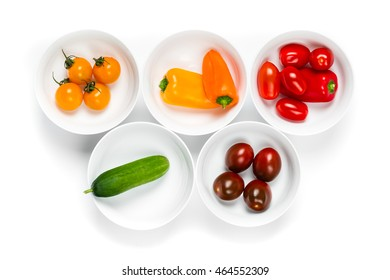 Set of white bowls full of fresh colorful vegetables top view close up