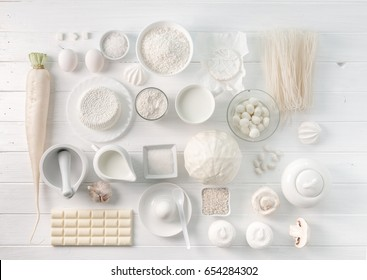 Set of white objects lying on the white wooden table, dairy products and tableware, topview