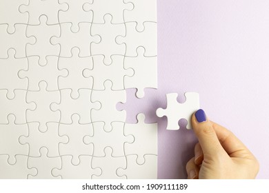 Set of white puzzle pieces and hand holding last one piece on purple background. top view
