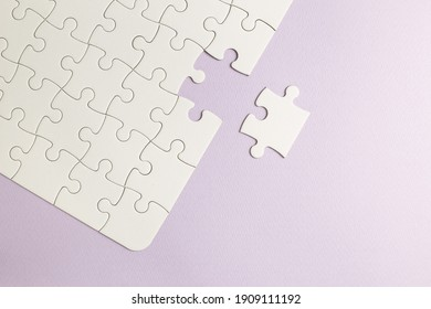 Set of white puzzle pieces and last one piece on purple background. top view