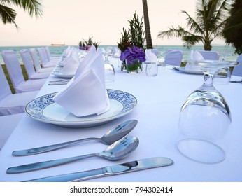 The set of white table and chairs for private dinner party on the beach including napkins, knifes, spoons, glasses and  waiting for the sunset time, romantic time.