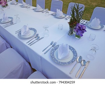 The set of white table and chairs for private dinner party on the beach including napkins, knifes, spoons, glasses and flowers  waiting for the sunset time, romantic time.