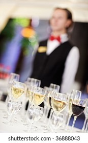 Set of wine glasses with waiter on blurred background. Shallow depth of field.