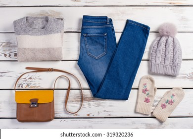 Set of winter clothes. Modern women's clothing on a wooden background.
