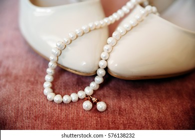 set of woman accessories. Pearl necklace and earrings on ivory wedding shoes. Jewelry, closeup