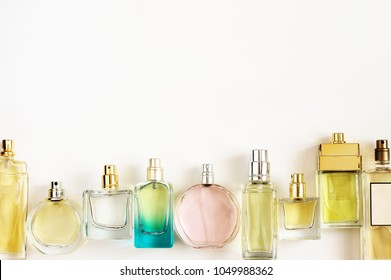 Set of woman perfumes lying in row on white background. Top view point.