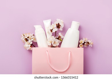 Set of woman's cosmetics in a bag with spring apricot bloom. Women's secrets. Spring female skin and hair care cosmetics in a bag on purple background. Cosmetic with apricot. Shampoo, lotion, tonic