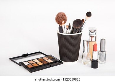 Set of woman's cosmetics on blue background. Women's secrets. Decorative cosmetics: highlighter, concealer, rouge, palette with eye shadows and brushes for face make up, face sculpture . Make up.