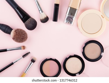 Set of woman's cosmetics on pink background. Women's secrets. Decorative cosmetics: highlighter, concealer, rouge, palette with eye shadows and brushes for face make up, face sculpture . Make up.
