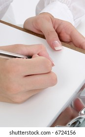 Set of woman's hands writing on clipboard with pen.