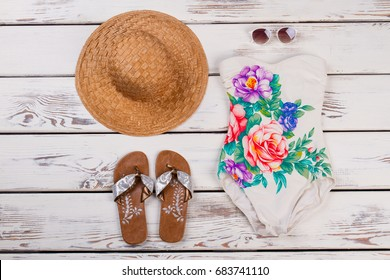 Set of women beach accessories. One-piece floral swimwear, straw hat, sandals and sunglasses on wooden background.