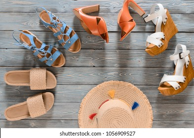 Set of womens shoes (wedges, heels and flat sandals) on grey wooden background. Spring summer collection. Flat lay. Template for online store, coupon, offer, promotion, discounts, gift card, deals