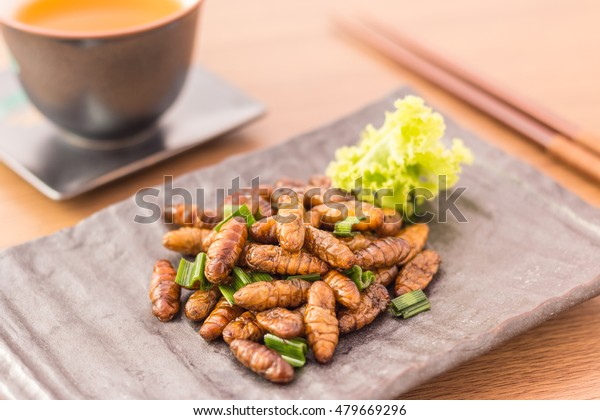 Set of Wood worm edible insect crispy mixed with pandan, Thai pepper powder,  lettuce in a brown plate with chopsticks, tea on wooden table background, Selective focus, Horizontal image