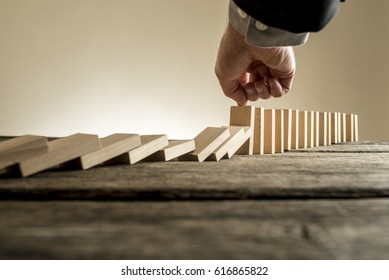 Set of wooden blocks, initially standing up vertically, with about 7 fallen down but a finger touching one block thus stopping further falls. Business concept of stop the rot.